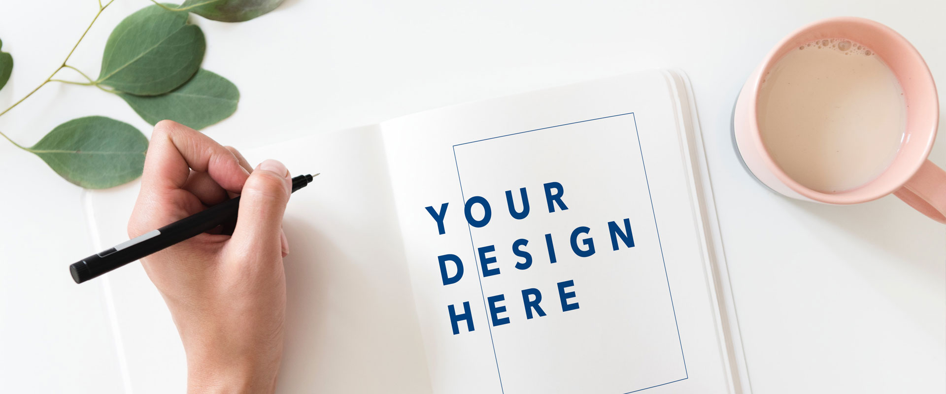 "image of hand on table with pencil and paper that reads ""Your Design Here"""