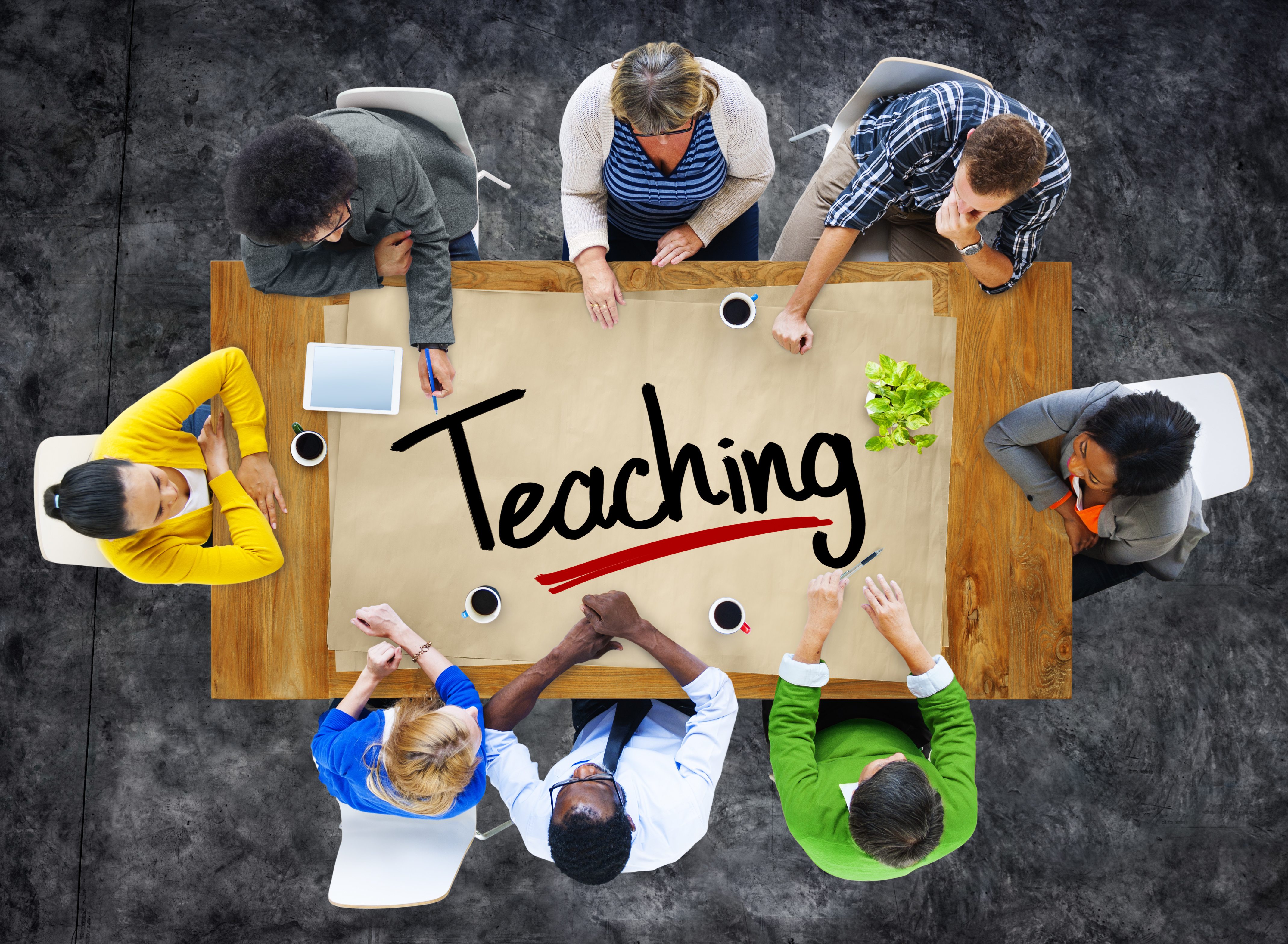 """students sitting around a table poster that reads """"teaching"""" on top"""