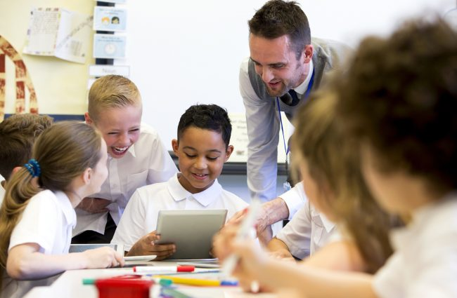 A male teacher sits supervising a group of children who are working on whiteboards and digital tablets.